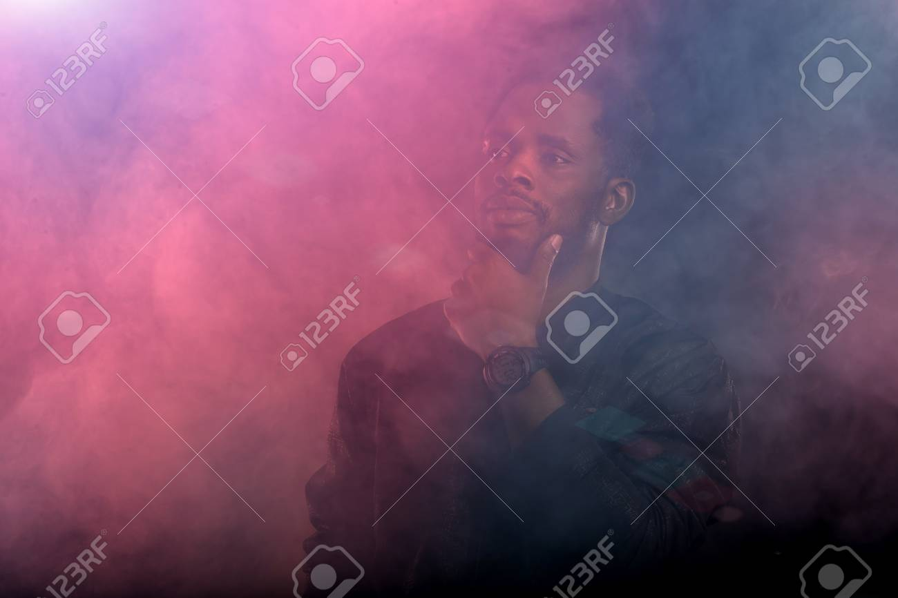 Portrait of brutal attractive black man with beard, full lips, touching chin looking away with thoughtful and dreaming expressions through the pink and blue smoke in dark. - 123053576