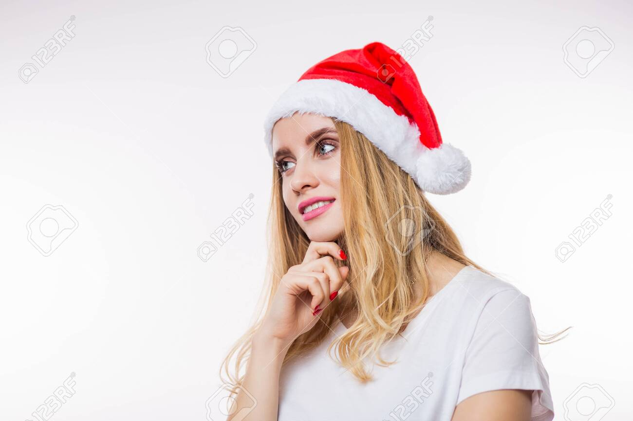 Happy charming blonde woman in red Santa hat and t-shirt looking with smile to the side on white background with copy space. Christmas, new year and celebration concept - 134834992