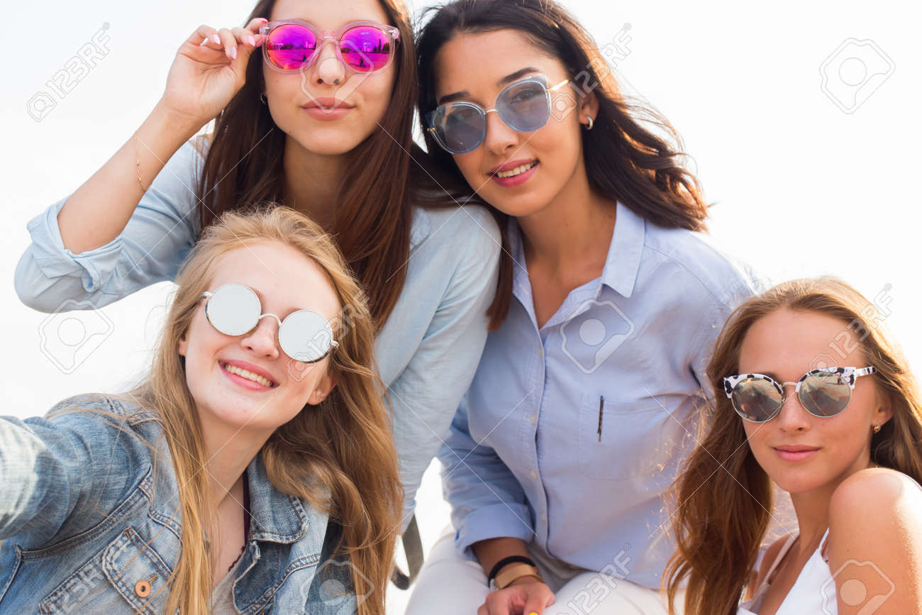 Close up portrait of four beautiful young student girl in colorful sunglasses on the background of the sky - 134966824