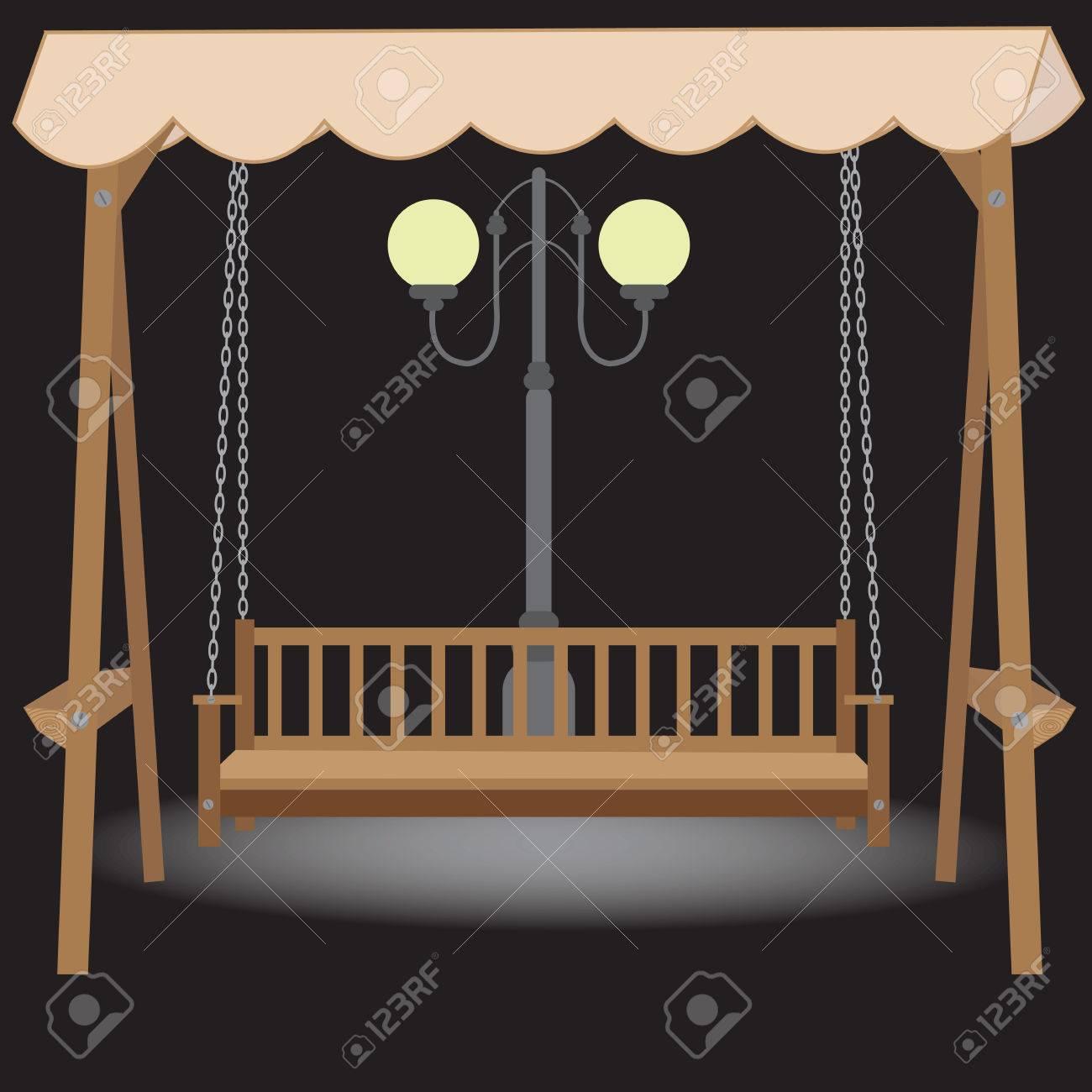 balancoire banc en bois avec un toit en tissu suspendu sur les chaines a la lumiere de la lampe de nuit