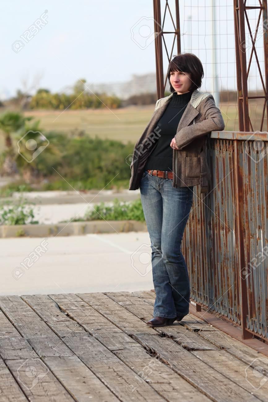 Terrasse Bois Et Fer une femme debout sur une terrasse en bois, en s'appuyant sur une clôture en  fer