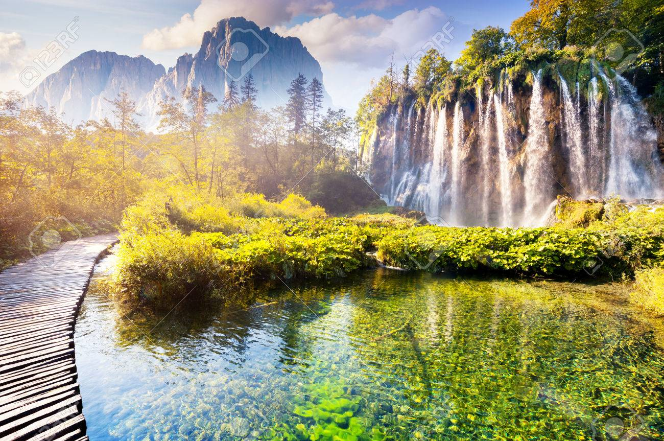 Majestic view on waterfall with turquoise water and sunny beams in the Plitvice Lakes National Park. Forest glowing by sunlight. Croatia. Europe. Dramatic morning scene. Beauty world. - 47565627