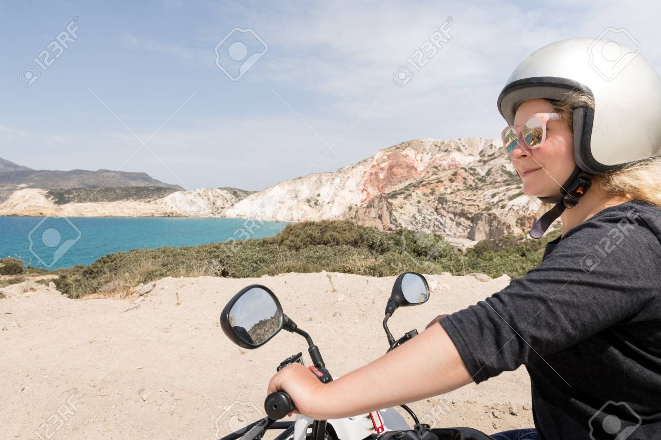 Young Woman Driving Rental Quad Bike On Seaside Road In Milos