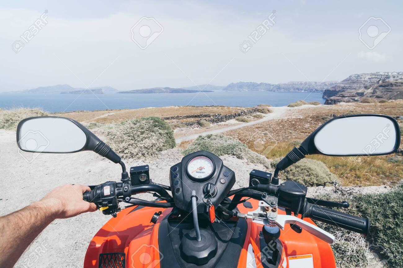 ATV quad bike driving along the shore of Aegean sea on Santorini island, Greece. View from driver seat - 136453102