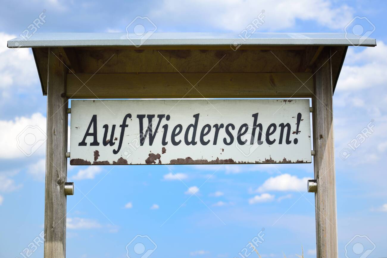 """On a white weathered sign reads """"Auf Wiedersehen"""" in German, against a blue sky with clouds. - 150595408"""