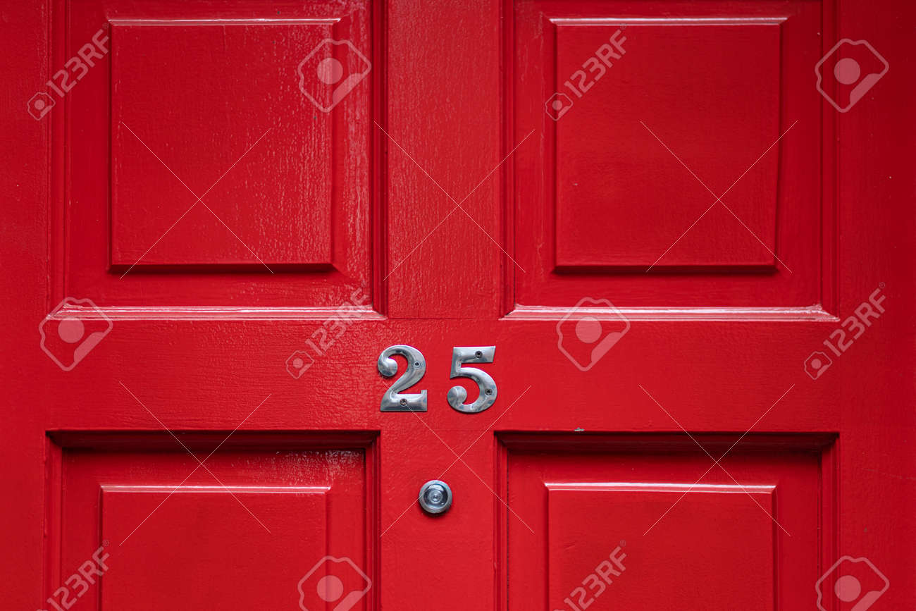 Detail of a red door with number 25 and peephole - 159103524