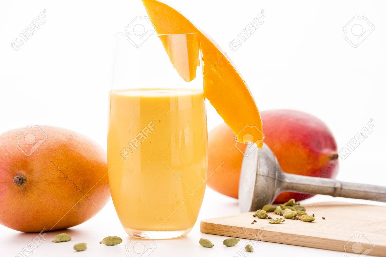 Mango Lassi In A Glass Decorated With A Cut Mango Fruit Chip Two Entire  Mangos