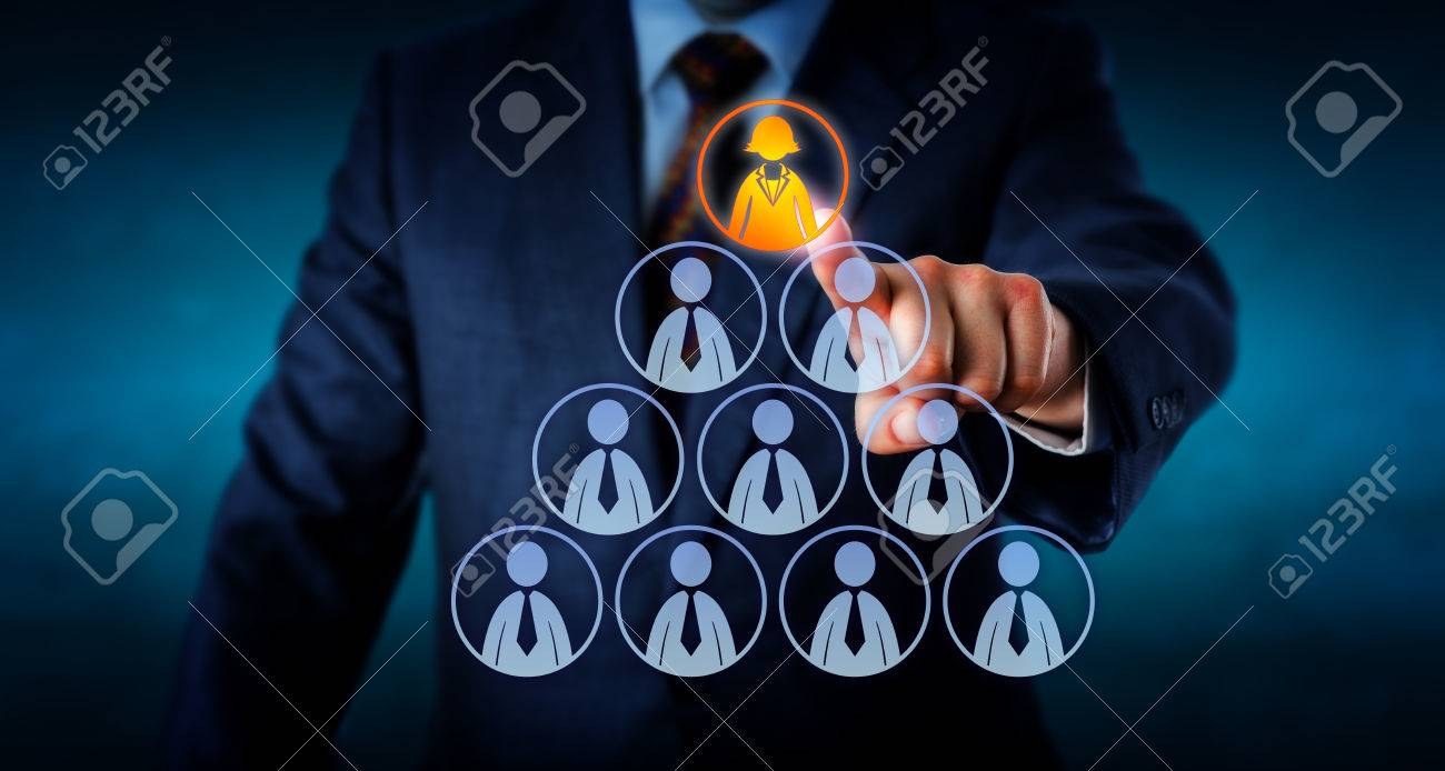 torso of a human resources manager is selecting a female office is selecting a female office worker atop a pyramid made out of otherwise male employee icons business metaphor for leadership headhunting and career