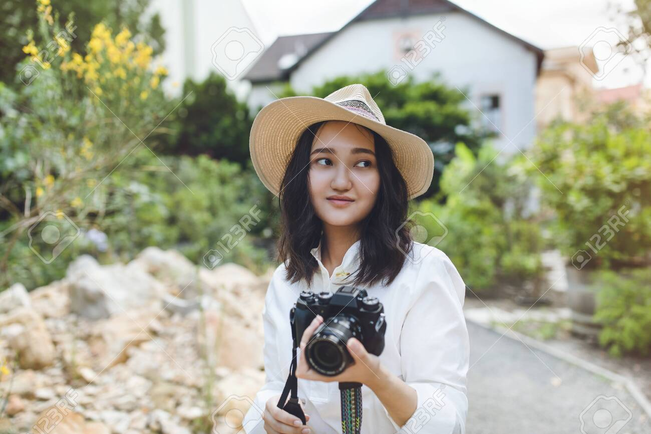Young asian woman in white shirt and hat in a park, smiling, holding camera. Outdoor portrait. - 140092289