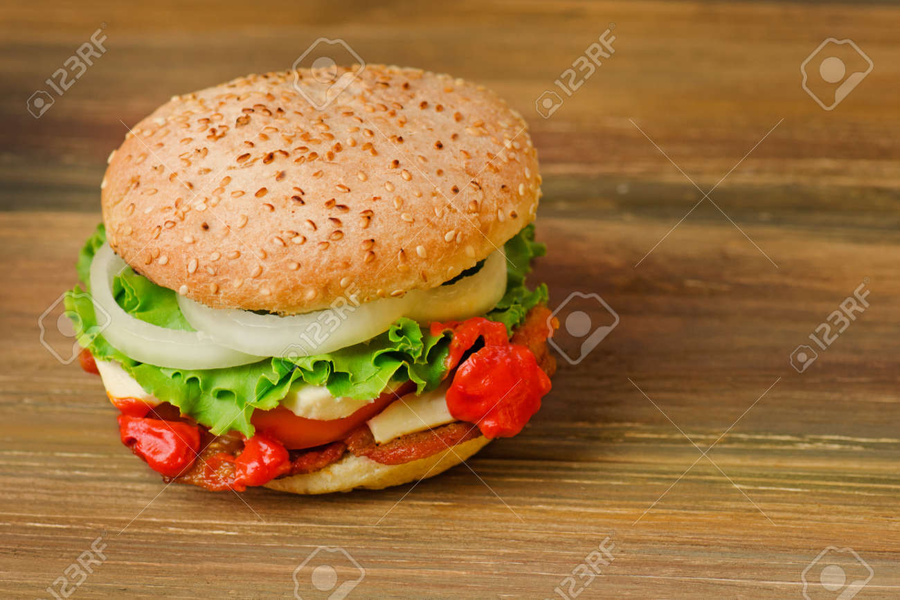 Preparation of delicious burger in a restaurant. Delicious burger on wood table background. Healthy chicken hamburger - 149834169