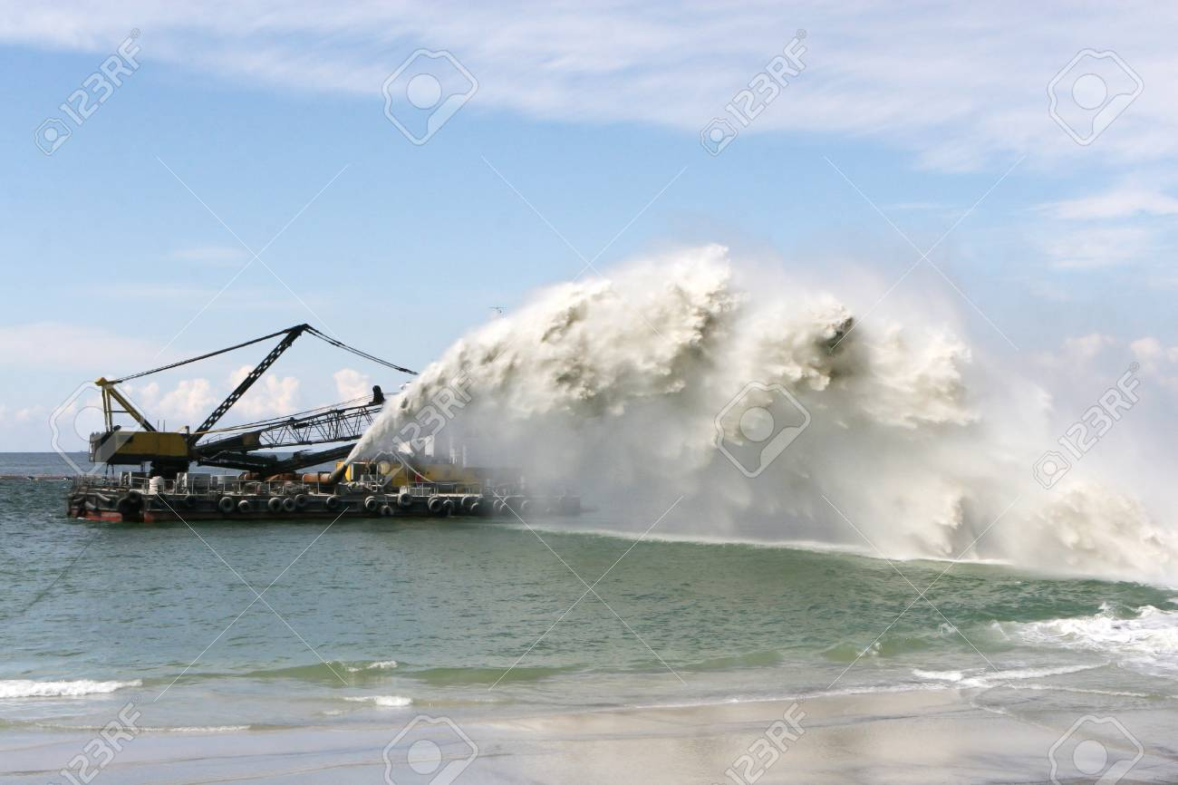 Work dredger dredging with sand washing on beaches. Special dredging hose for sand to create new land. Sand washing on sea beaches. Dredging, washing out sand on beach during construction sea terminal - 115172370