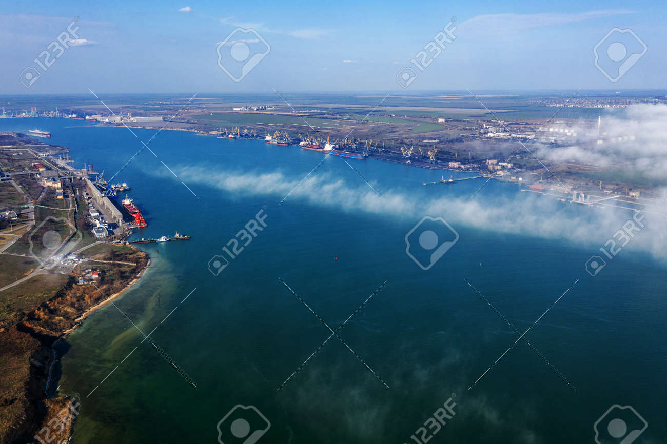 Aerial view of panoramic seaport warehouse and container ship, crane vessel working for delivery of delivery containers. Yuzhny Sea Industrial Port, Port Plant, Ukraine, 2019. Ships in sea port, fog - 121544809