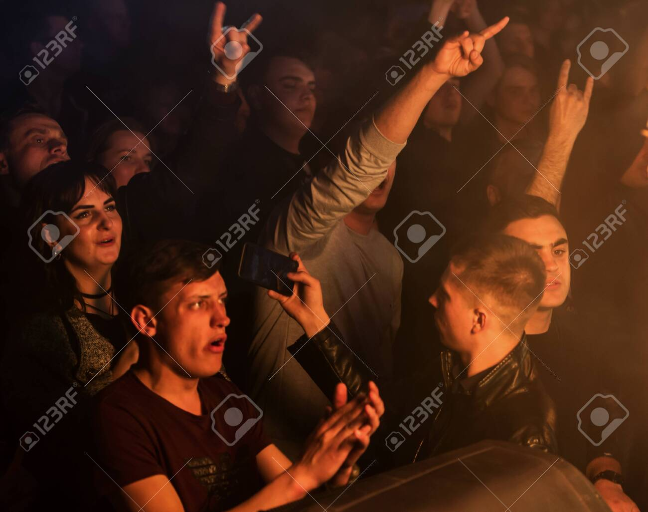 ODESSA, UKRAINE - March 23, 2019: viewers in auditorium of concert hall emotionally meet their favorite performers. Audience in theater hall. Viewers like performance on stage - 127883269