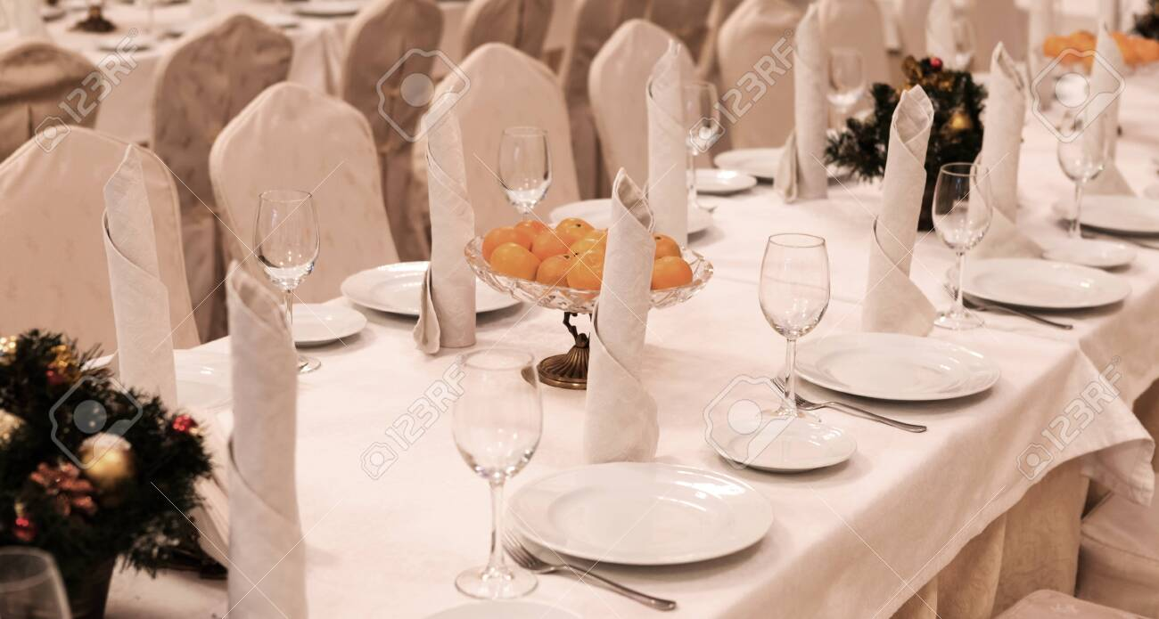Festive table setting background. Serving a large festive restaurant table in anticipation of guests in a soft dim light. - 144697364