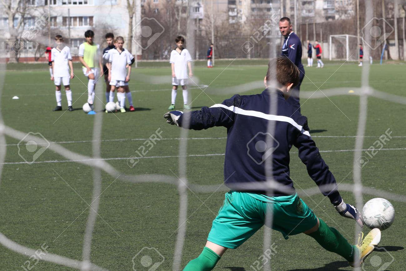 Odessa, Ukraine - April 7, 2021: Local children's football teams U-14 play on artificial grass of stadium. Football on field with artificial grass for soccer games. Children are playing football - 167820160