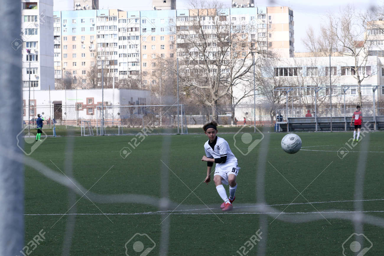 Odessa, Ukraine - April 7, 2021: Local children's football teams U-14 play on artificial grass of stadium. Football on field with artificial grass for soccer games. Children are playing football - 167820139