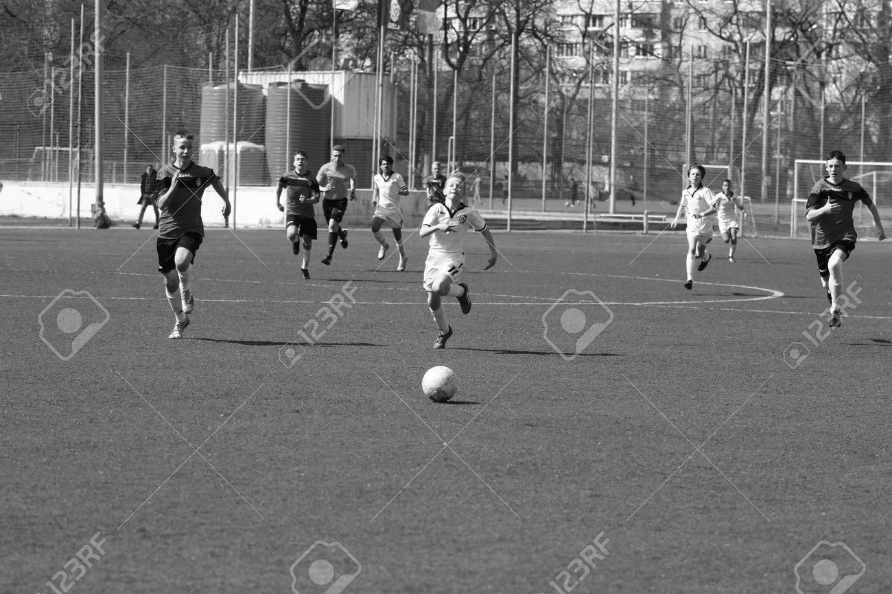 Odessa, Ukraine - April 7, 2021: Local children's football teams U-14 play on artificial grass of stadium. Football on field with artificial grass for soccer games. Children are playing football - 167820158