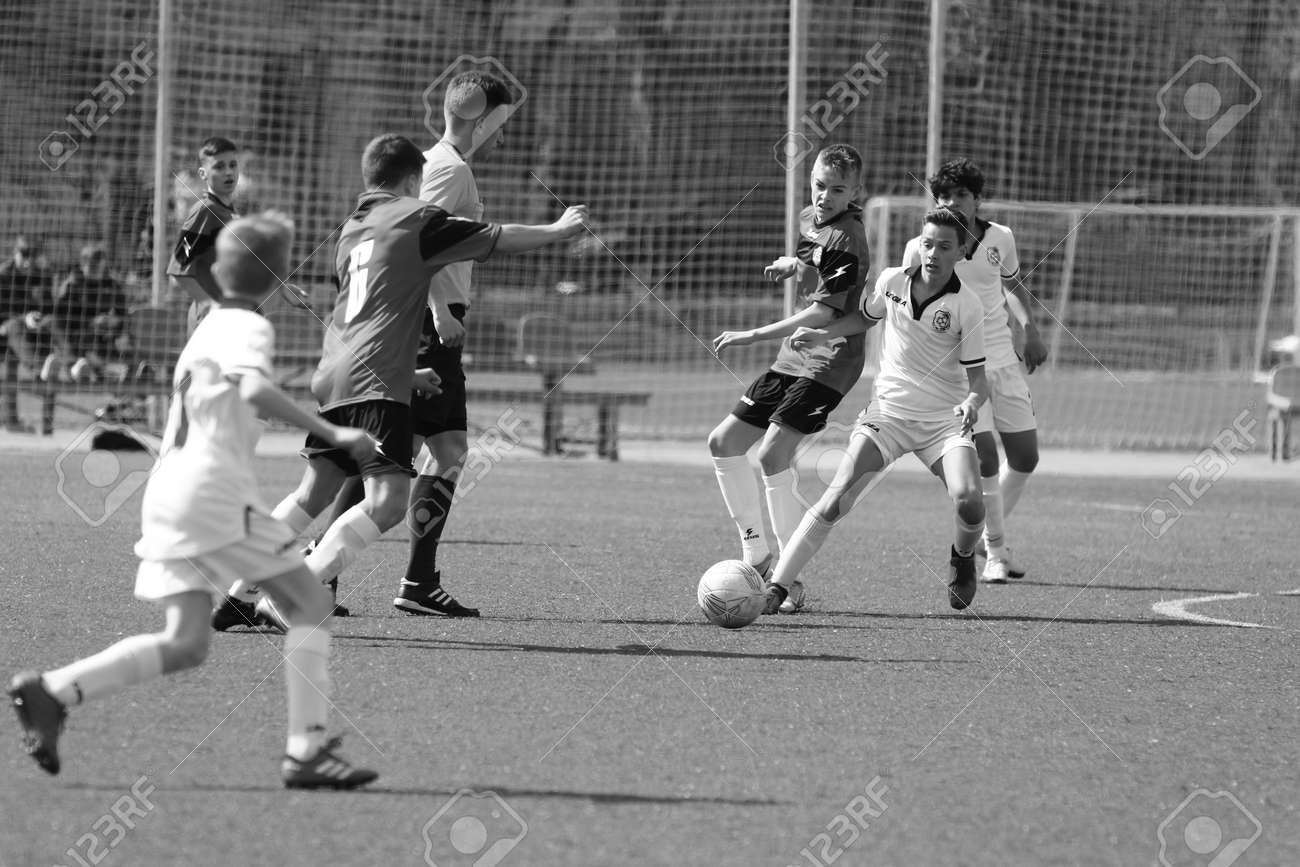 Odessa, Ukraine - April 7, 2021: Local children's football teams U-14 play on artificial grass of stadium. Football on field with artificial grass for soccer games. Children are playing football - 167820140