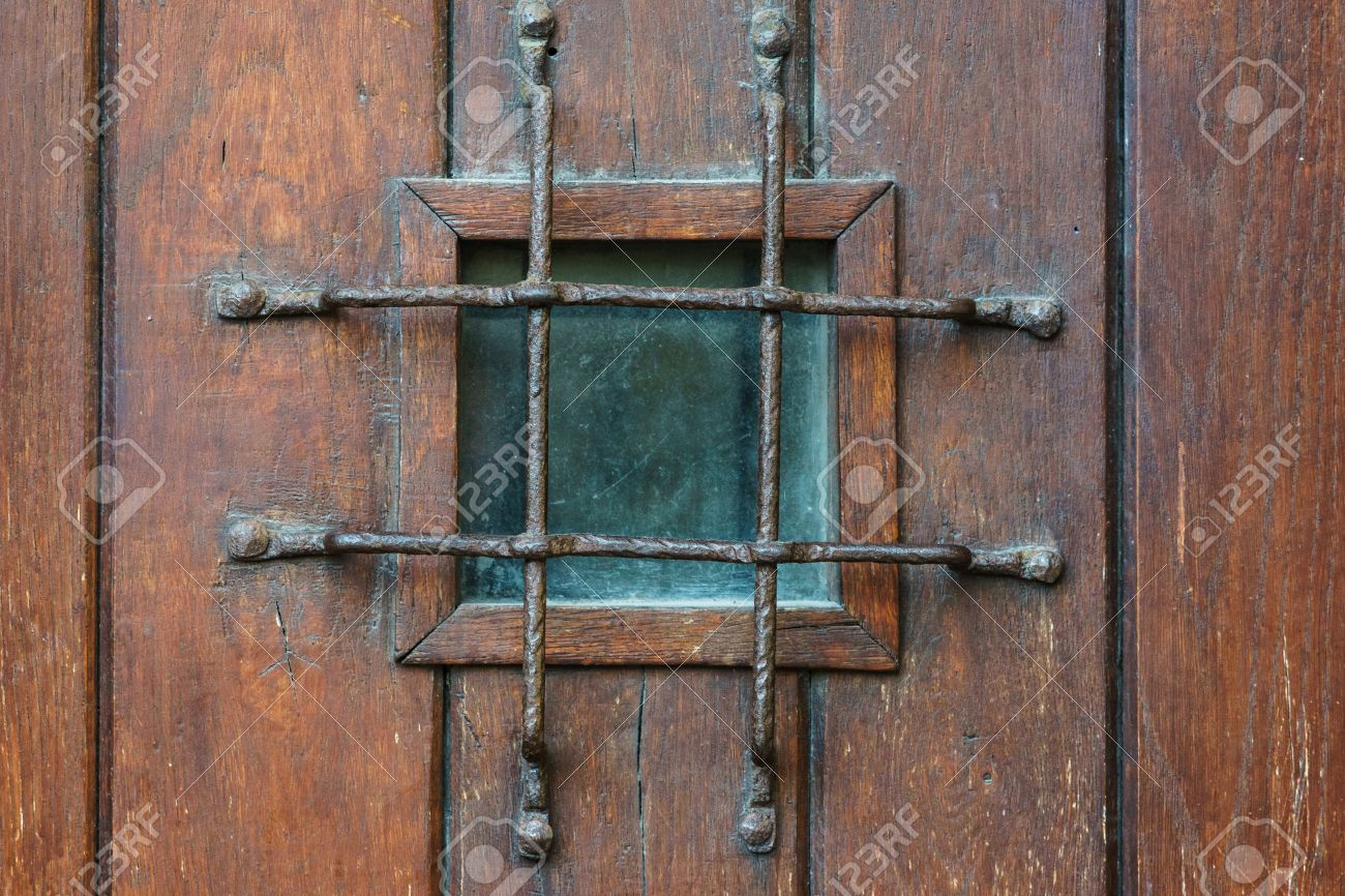 Genial Small Square Window With Grate In Old Style Wooden Door, Confinement  Concept Stock Photo