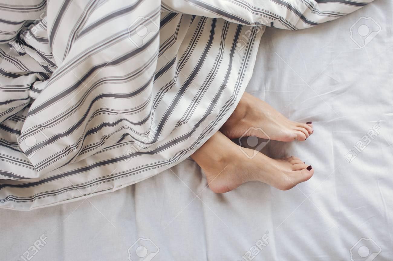 58773c322c Sleeping woman feet under blanket. Beautiful feet of sleeping woman under  the blanket on her