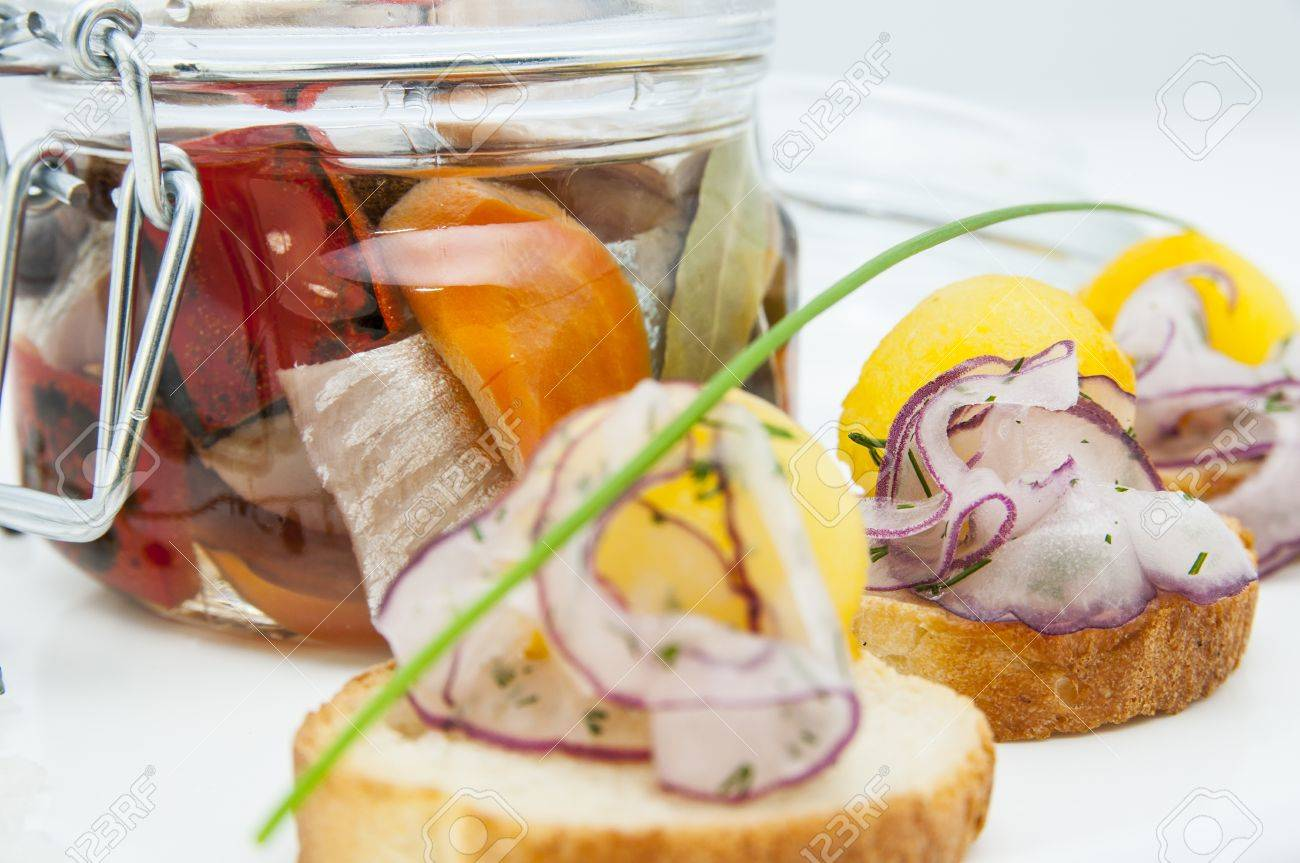 pickled herring in a glass jar with potato canapes Stock Photo - 16344227