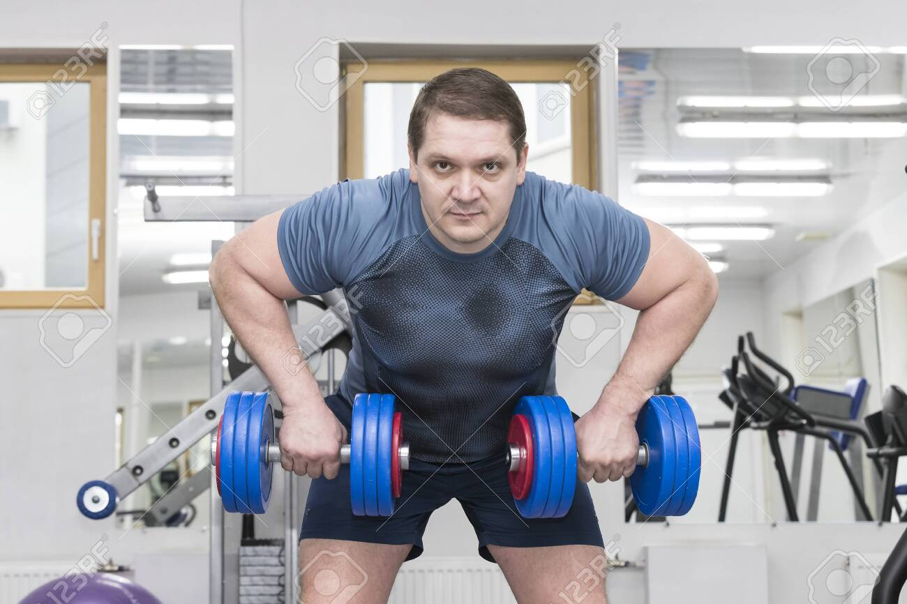 Middle-aged man goes in for bodybuilding in the gym. - 130752104
