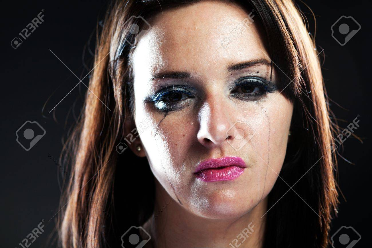 Hurt woman crying, face with smeared make up on dark background Stock Photo - 28211553