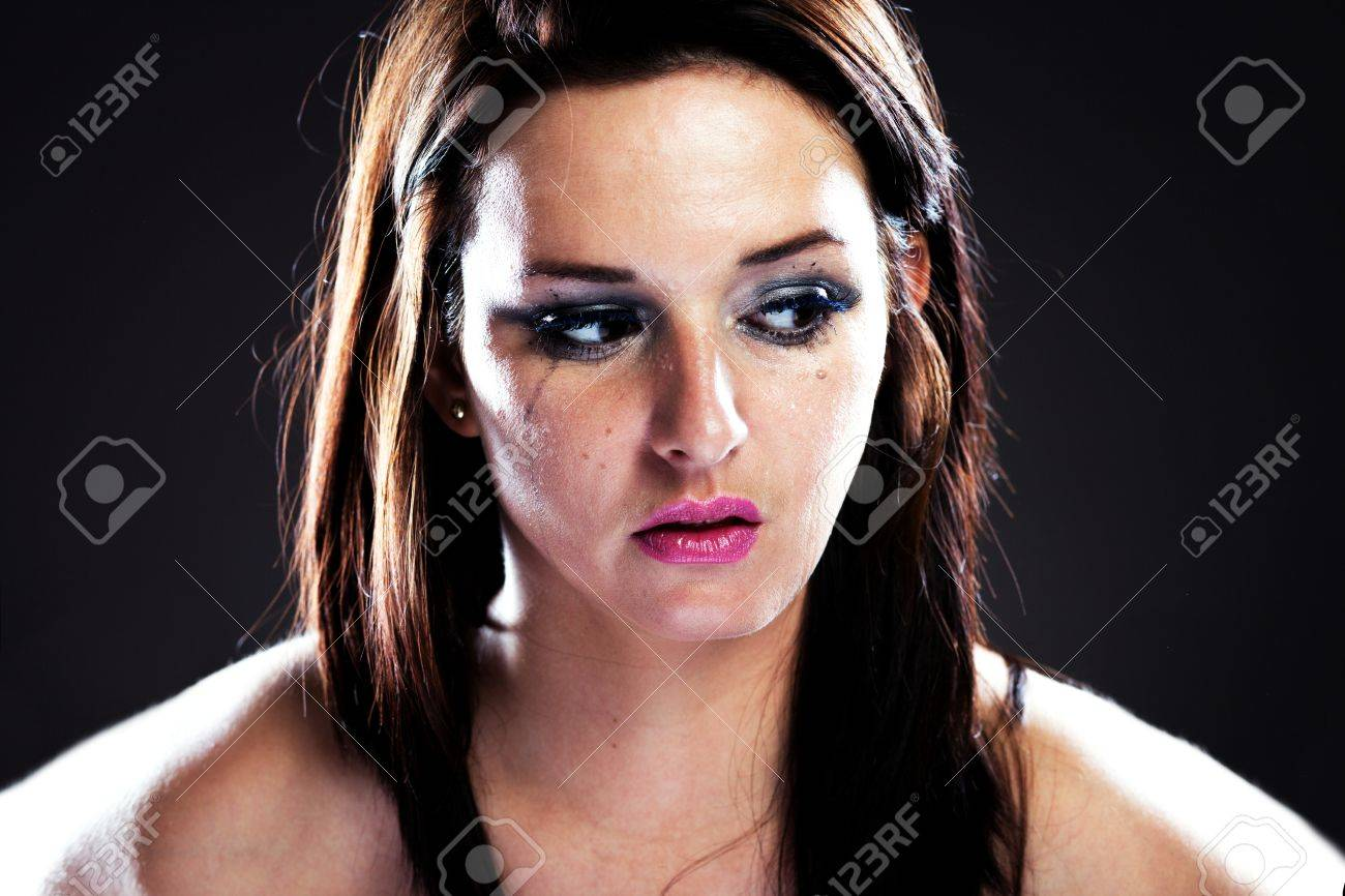 Hurt woman crying, face with smeared make up on dark background Stock Photo - 28211583