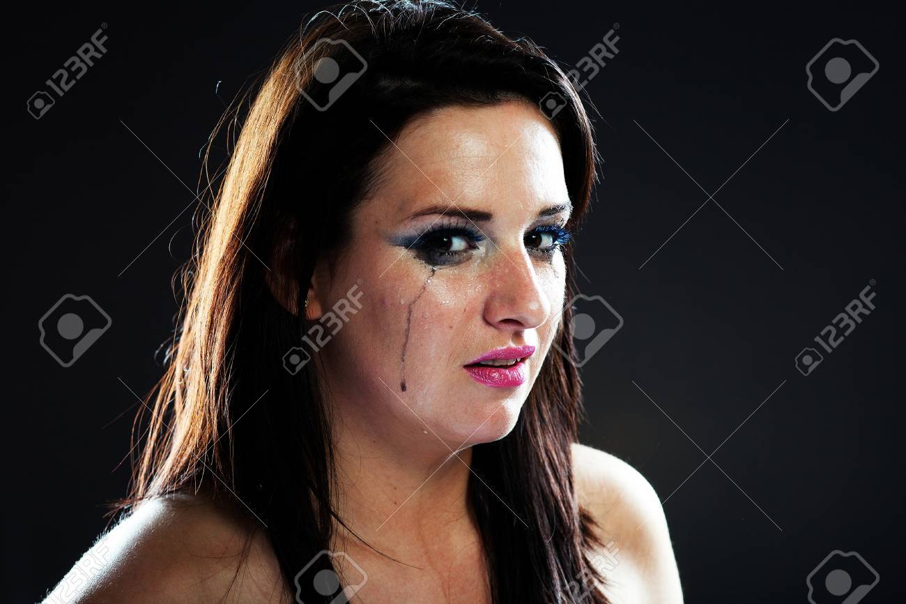 Hurt woman crying, face with smeared make up on dark background Stock Photo - 28211599