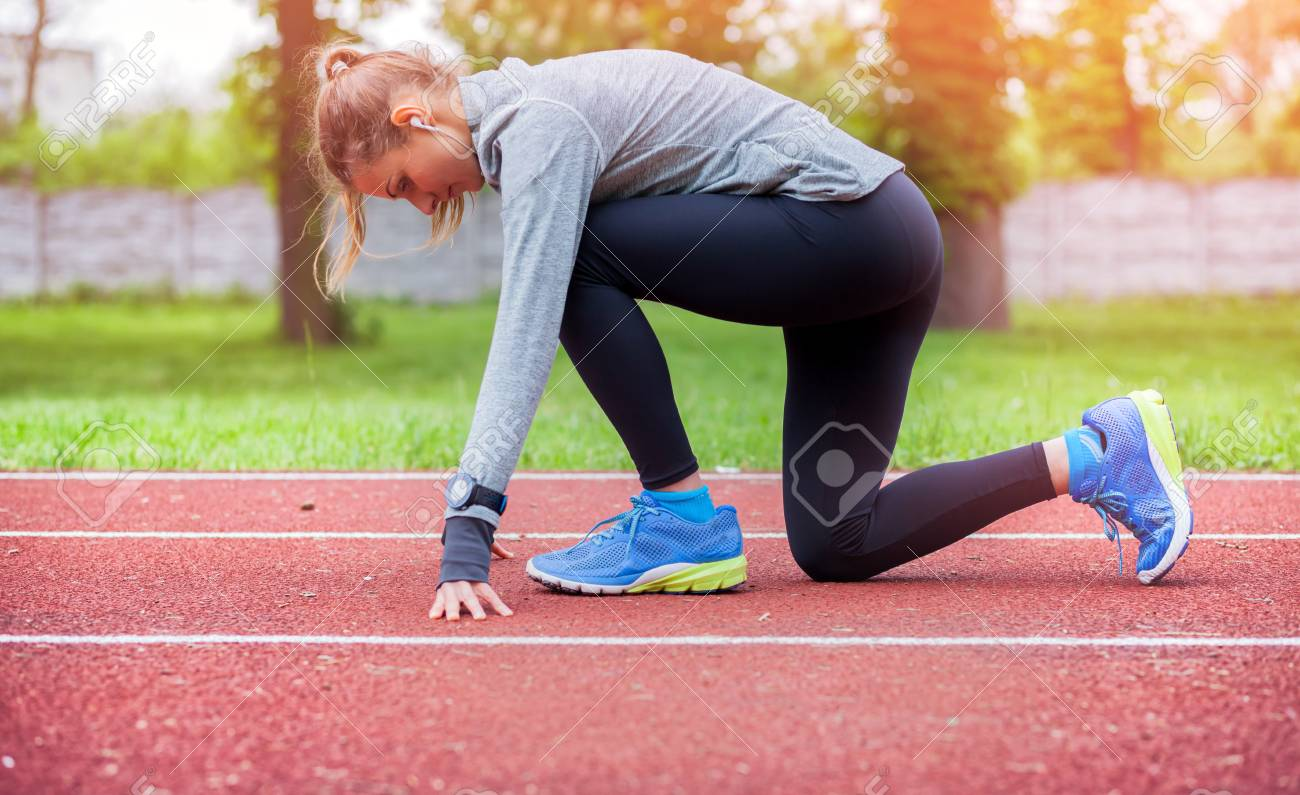 Athletic Woman On Running Track Getting Ready To Start Run Stock Photo