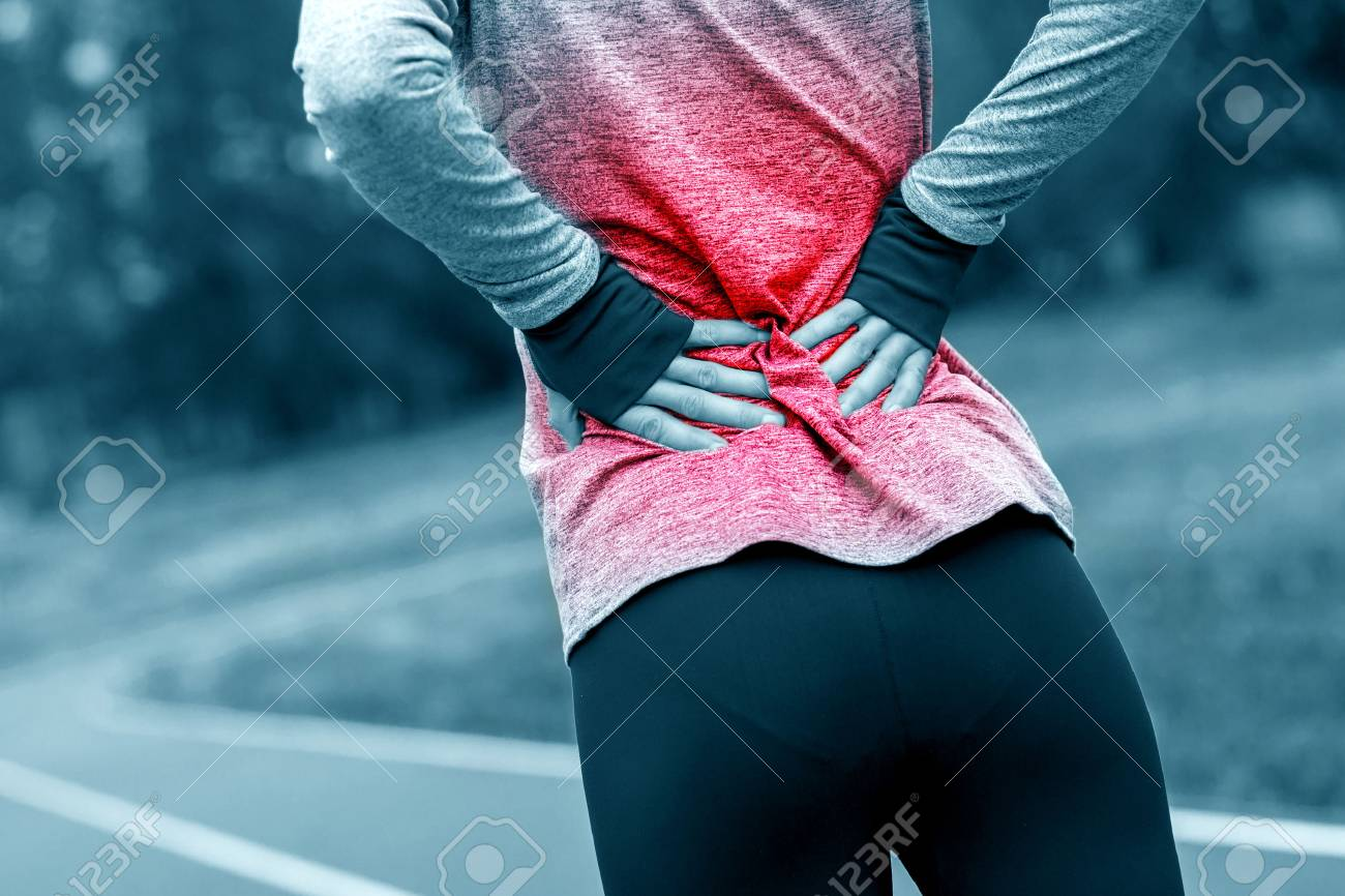 Athletic woman on running track touching hurt back with painful injury during workout - 80602921