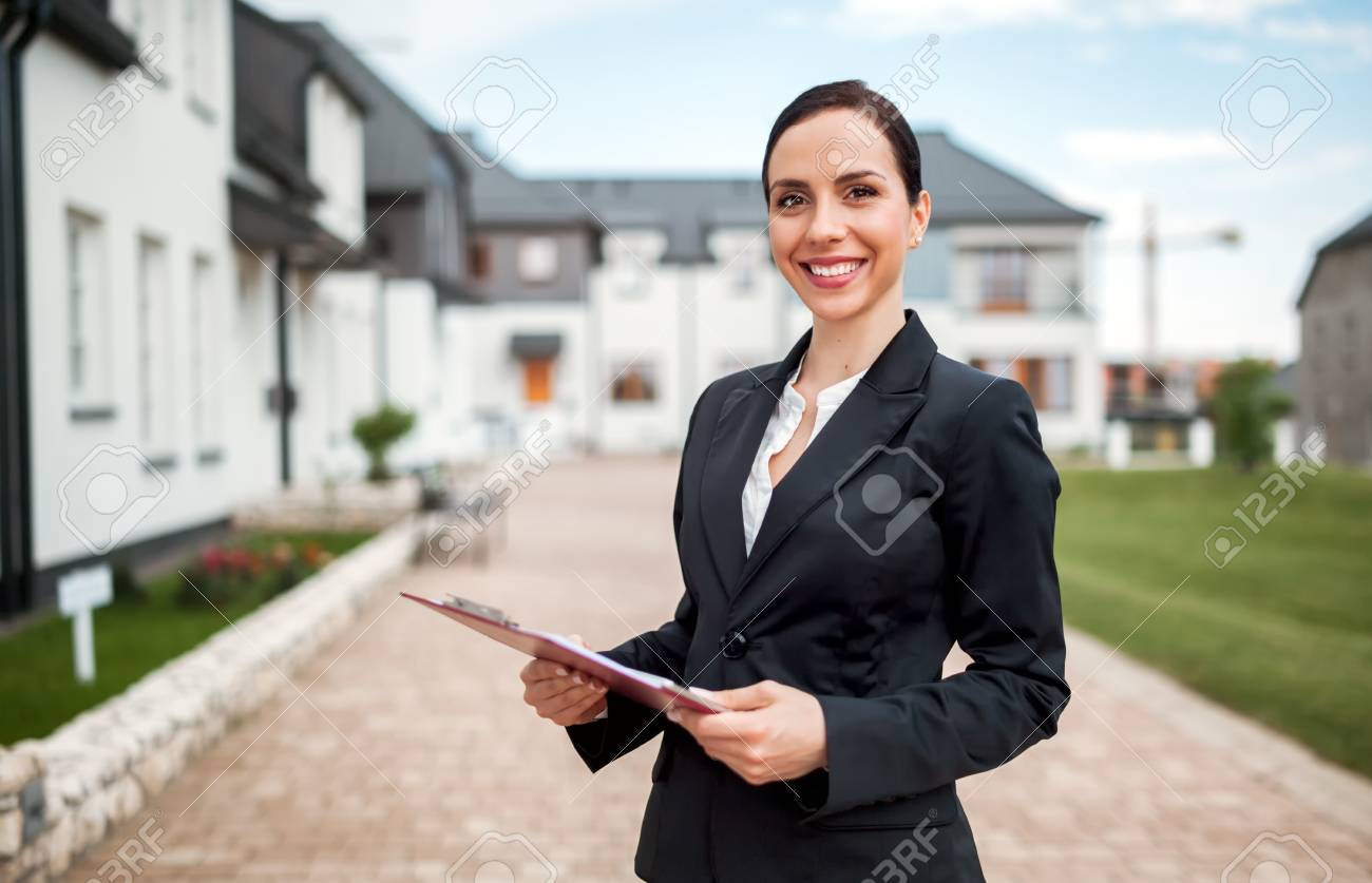 Real estate agent in front of house for sale ready to presenting offer, copy space - 104289033