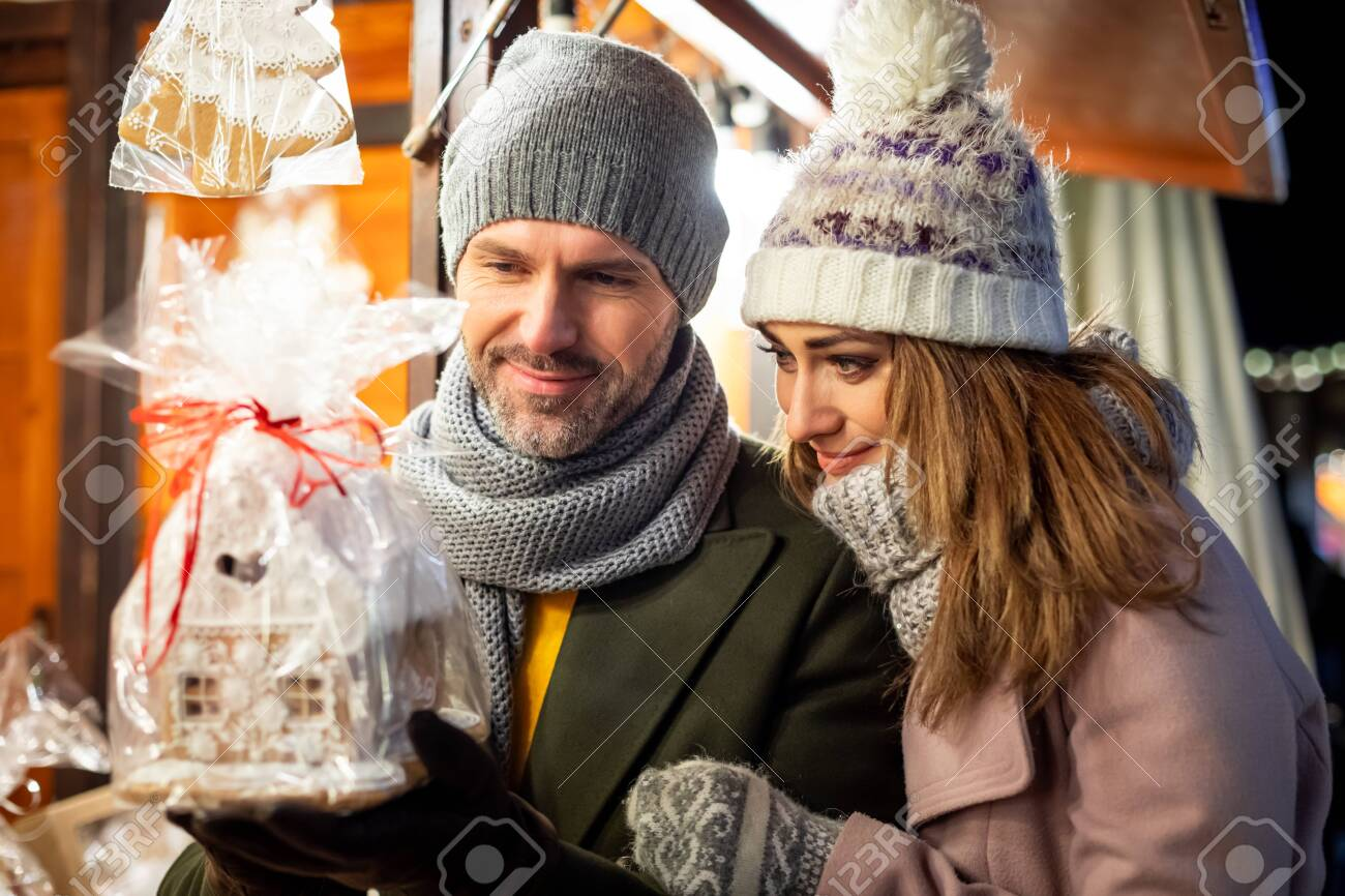 A nice couple spends time together at the Christmas market looking at products in the stalls - 135893044