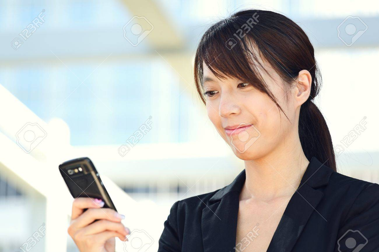 Business woman sending text message on mobile phone Stock Photo - 9996288