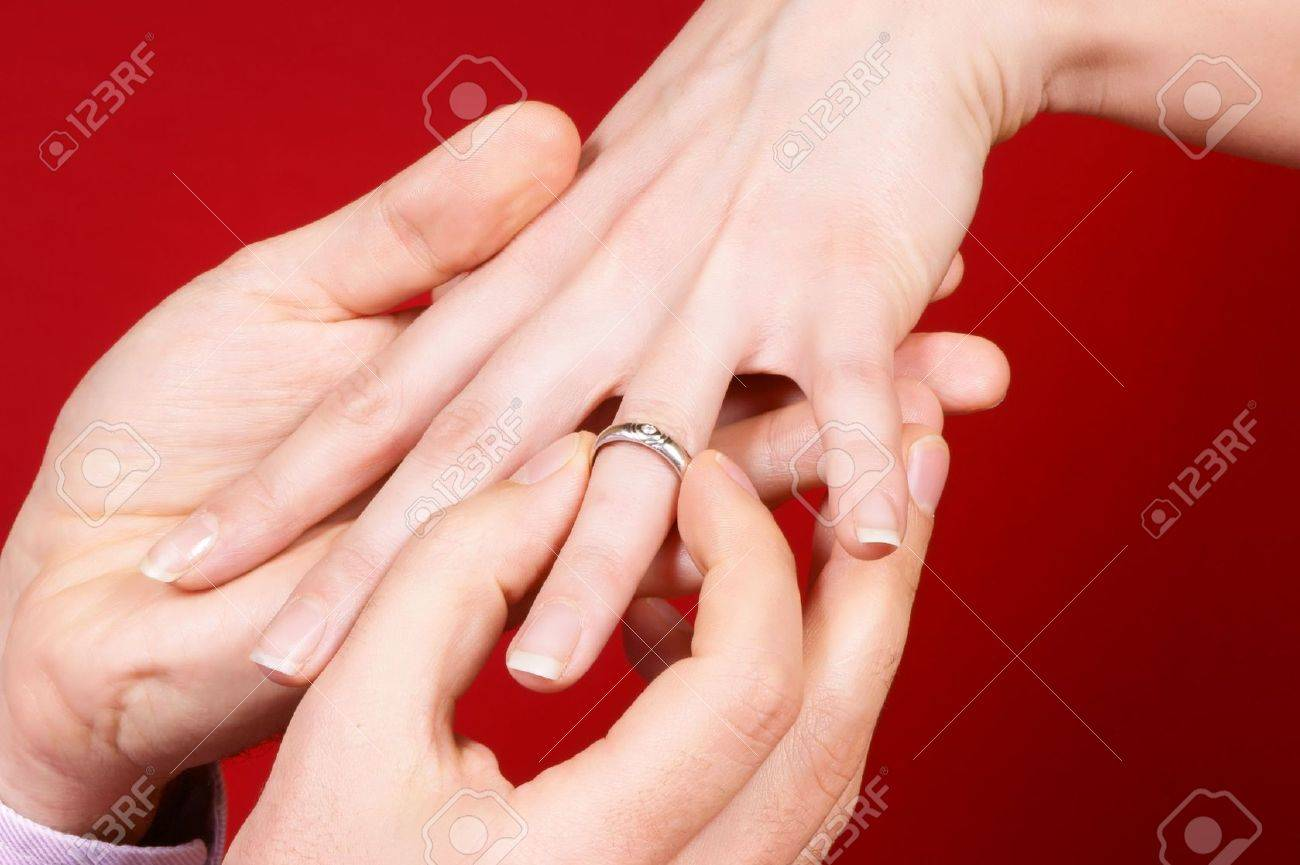 Man Putting An Engagement Ring On A Woman\'s Hand Over Red Background ...