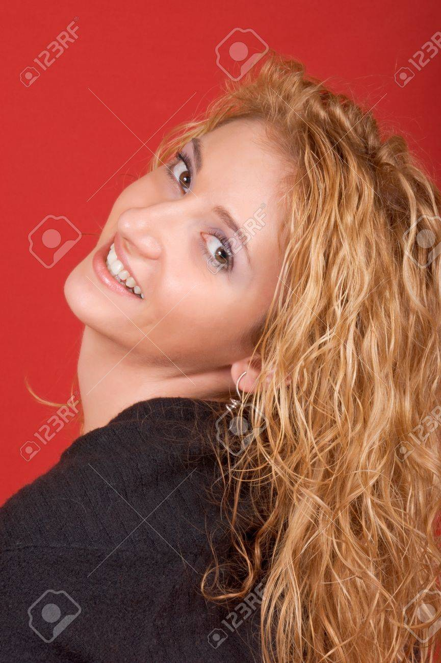 Beautiful young woman looking over shoulder and smiling. Studio shot over red background Stock Photo - 8193800