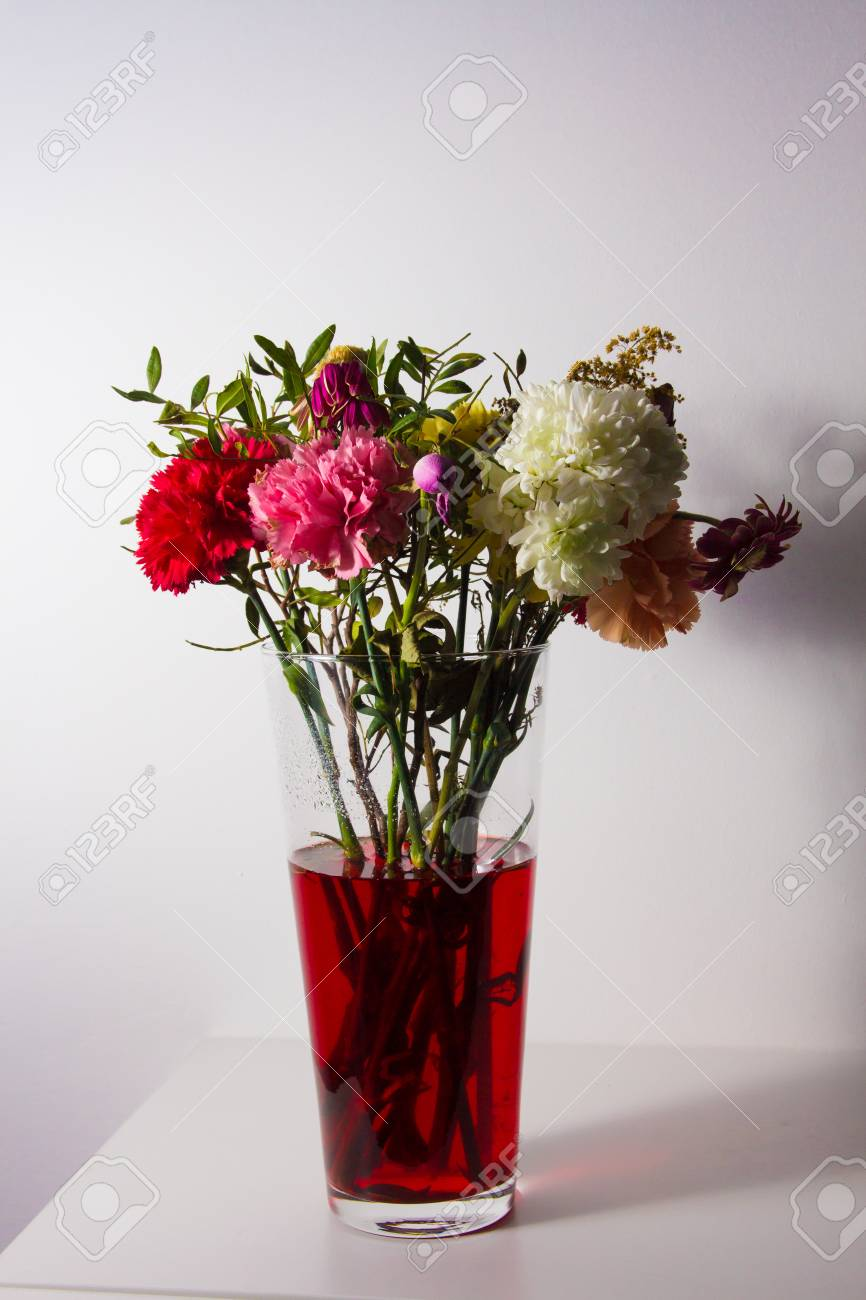 Flowers Just Starting To Wilt In A Tall Transparent Vase And Stock