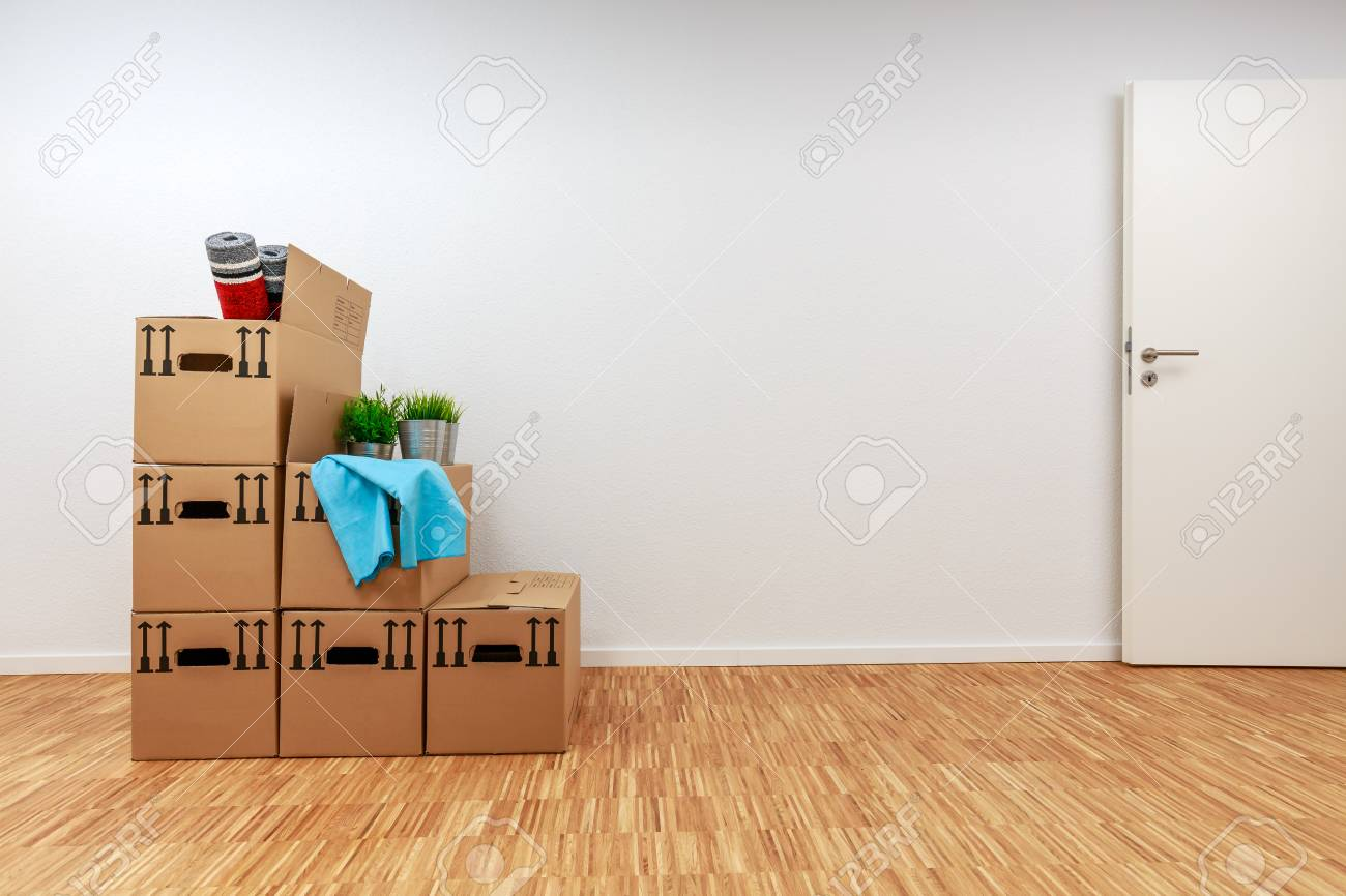 Moving cartons in empty white room with wooden parquet - 122186972