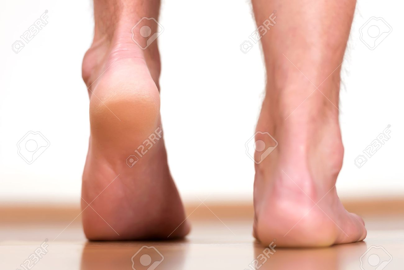 Pair of male feet stepping - view from back. - 46471106