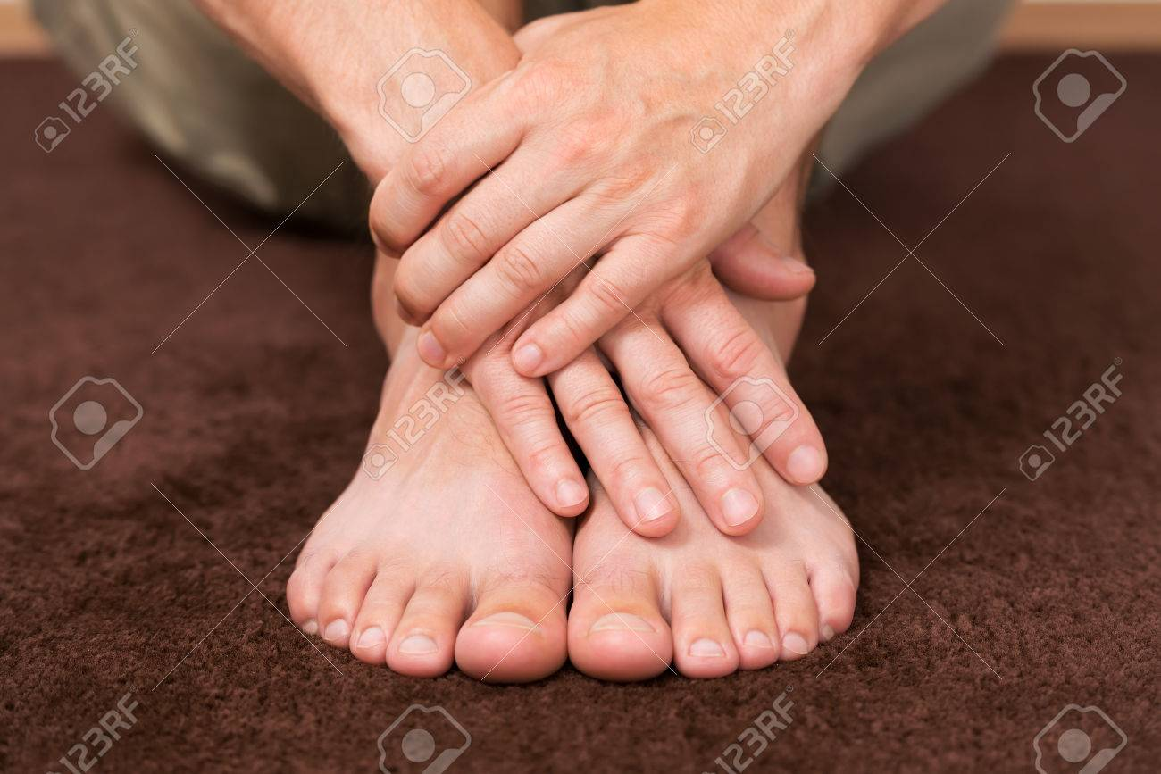 Male hands crossed over healthy resting feet. - 60324293