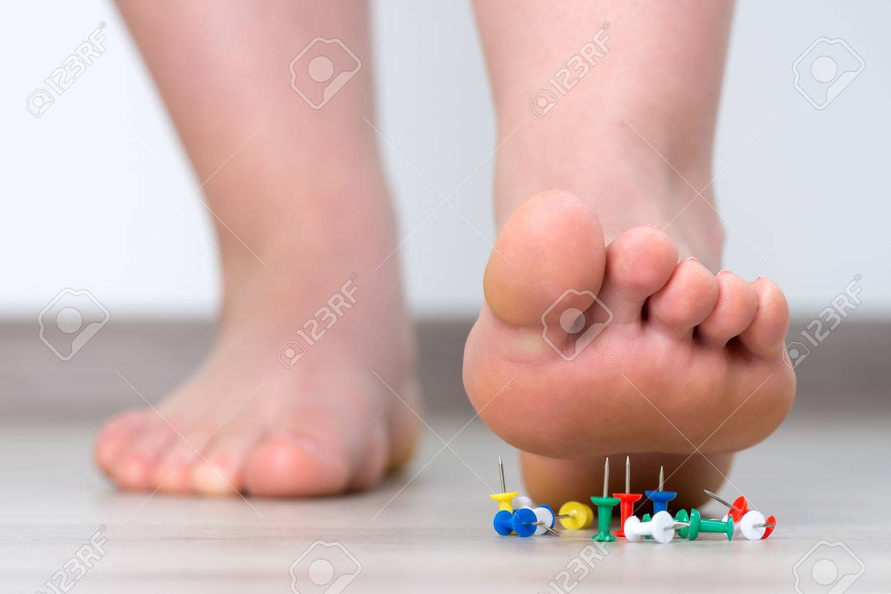 Female foot above colored pushpin - 63627348