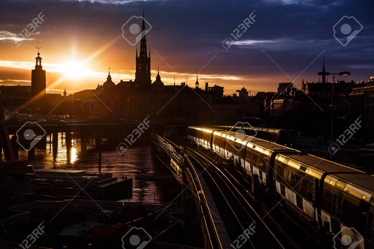 Stockholm city skyline. The view of Old Town, Gamla Stan, and Riddarholmen Church from The Central Bridge Centralbron with local trains on it during sunset. Sweden. - 131899002