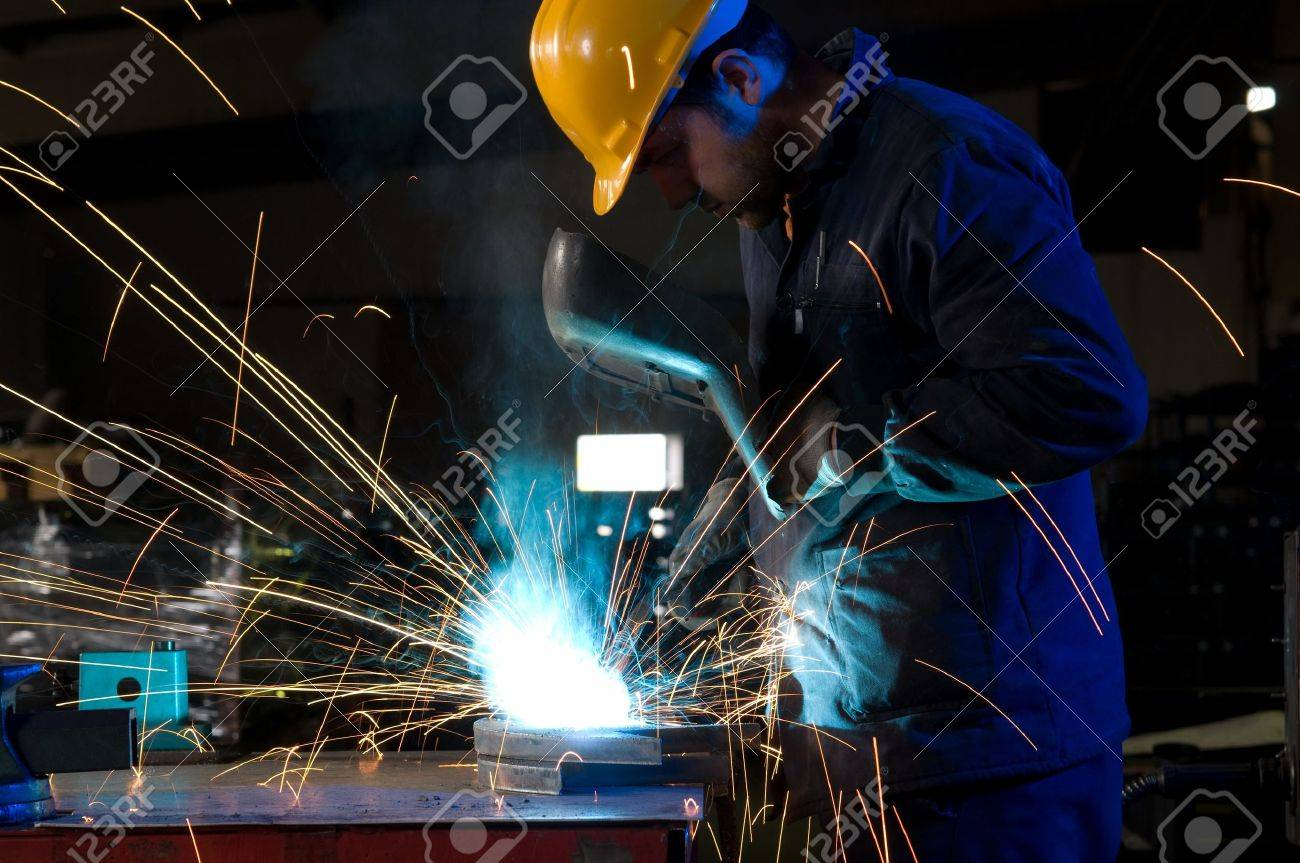 Worker making sparks while welding steel isolated Stock Photo - 14287476