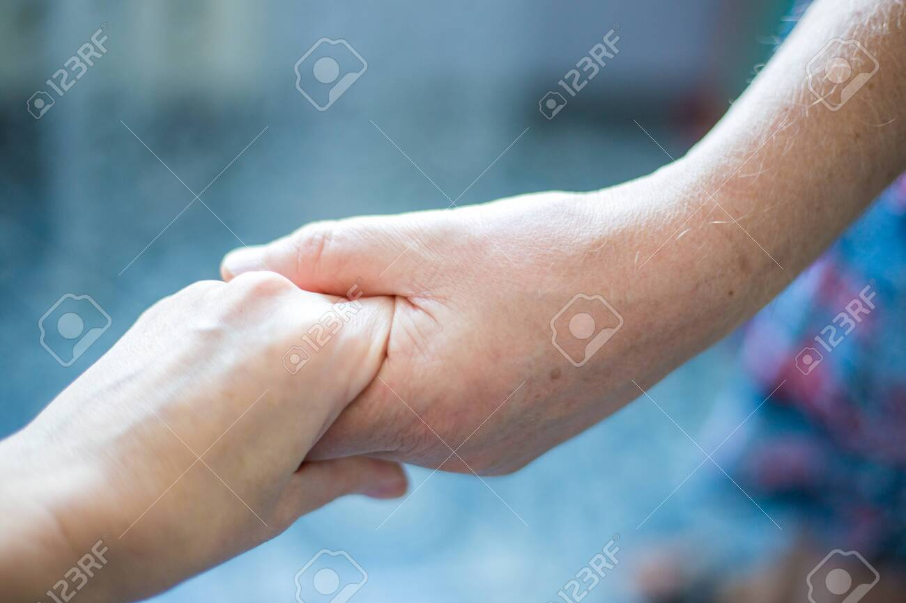 female hand in a male hand holding each other - 136984648