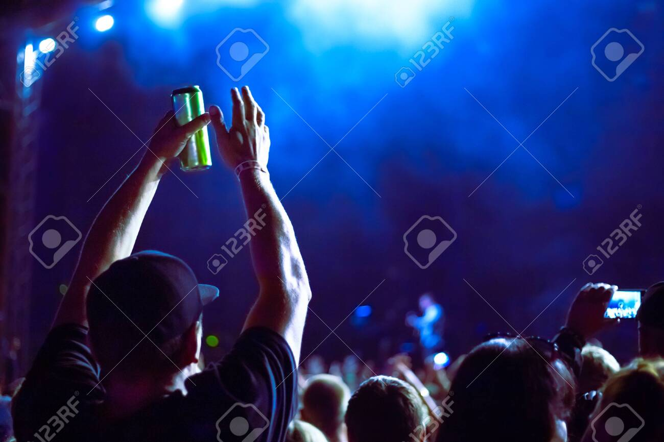 A man holds a can of beer and claps his hands at a music festival - 141888185