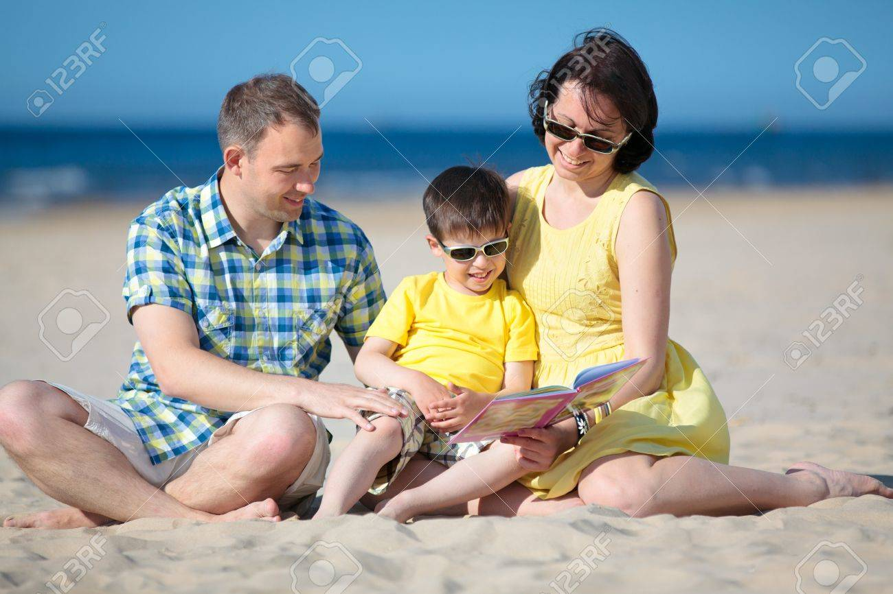 Parents reading book to their child on tropical beach Stock Photo - 14127814