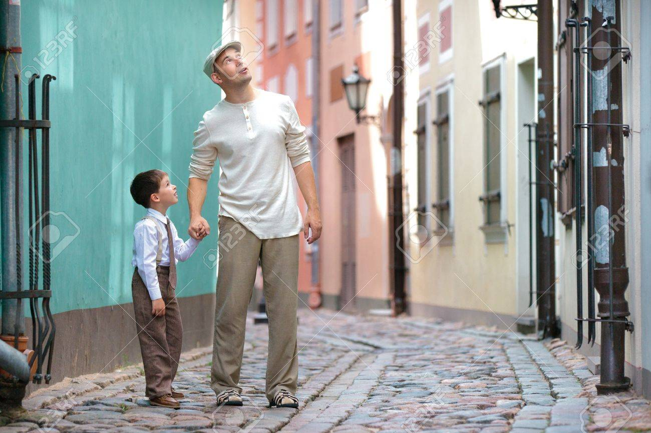 Father and son walking outdoors in city on beautiful summer day Stock Photo - 14980593