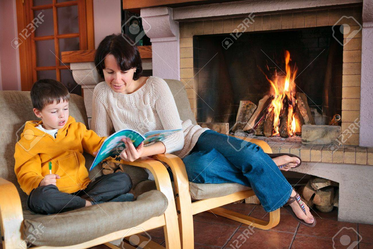 Mother And Son Reading A Book In Front Of Fireplace Story Time