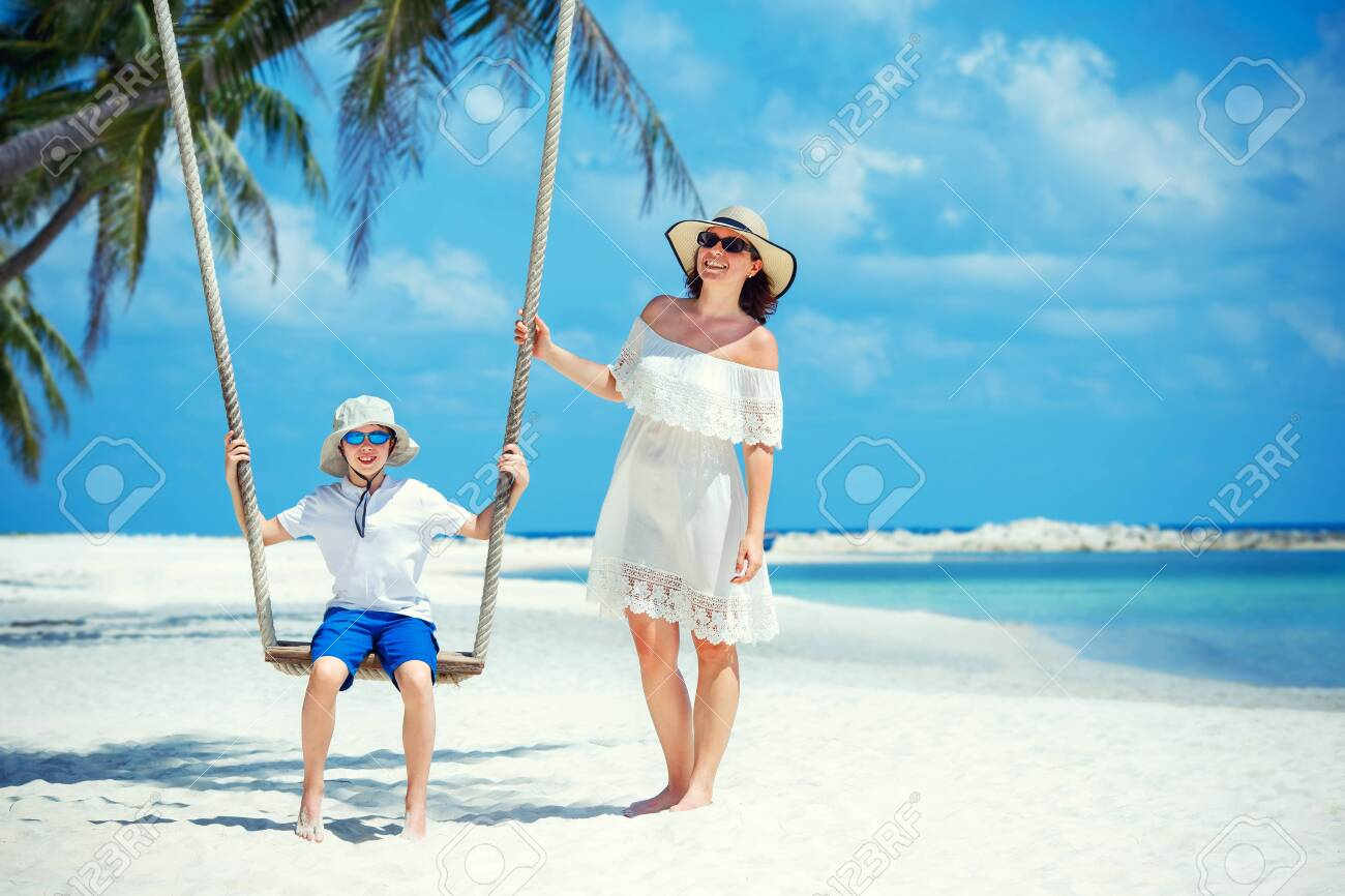 Young beautiful woman swinging her son on a tropical beach, Koh Phangan island. Thailand, Asia - 122800696