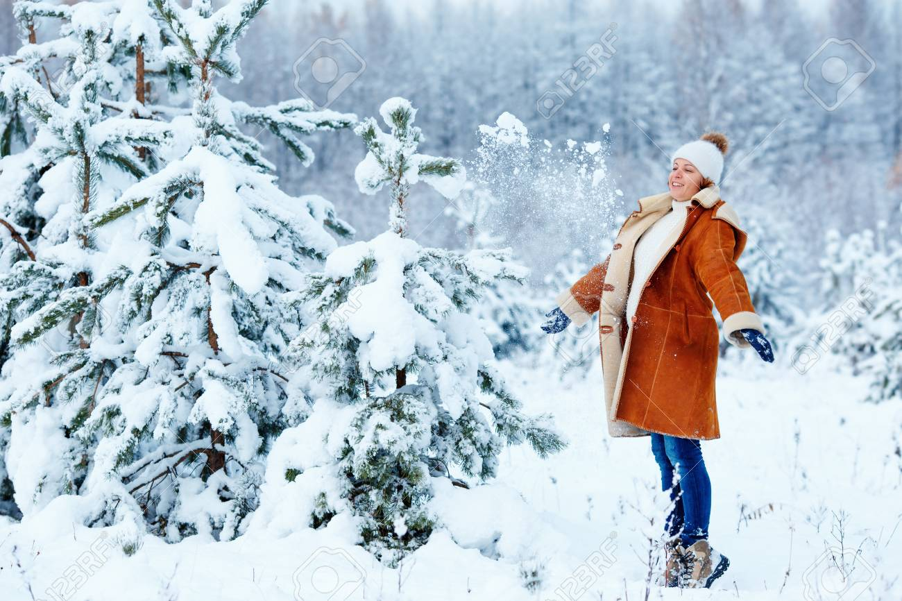 1bf15f2cb9 Stock Photo - Young pregnant woman wearing warm clothes having fun on  beautiful winter snowy day